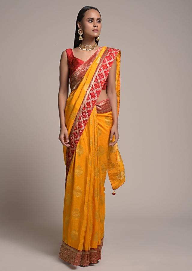 Amber Yellow Saree In Dola Silk With Brocade Leaf Shaped Buttis And Contrast Red Bandhani Border Online - Kalki Fashion