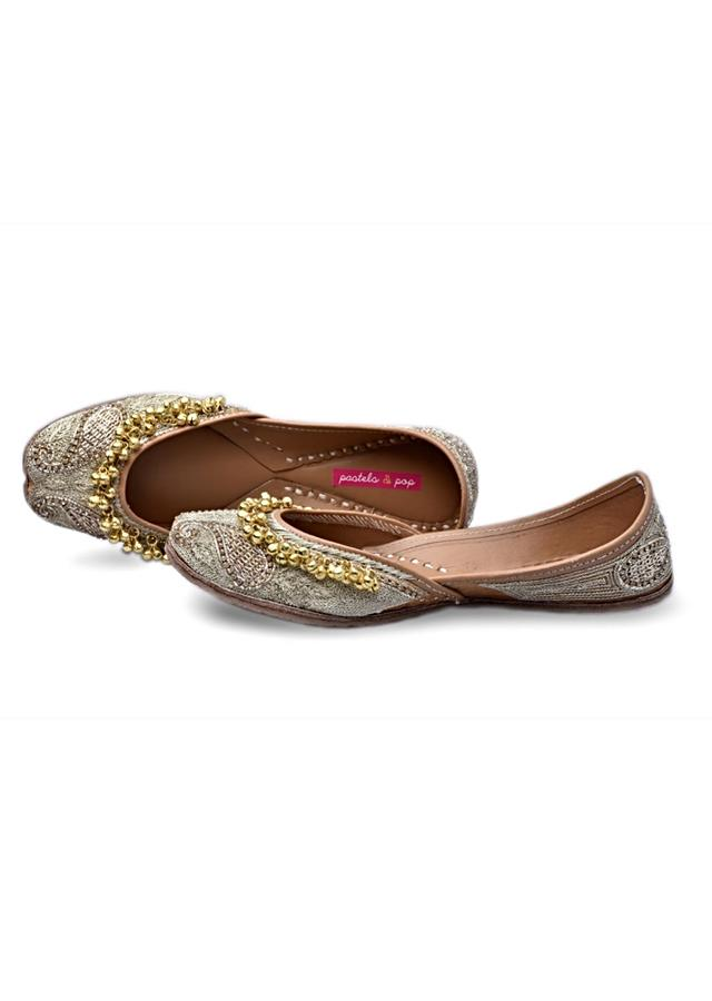 Beige Base Juttis With Gold Zari Work, Embellished With Crystals And Ghungroo Tassels By Pastels And Pop