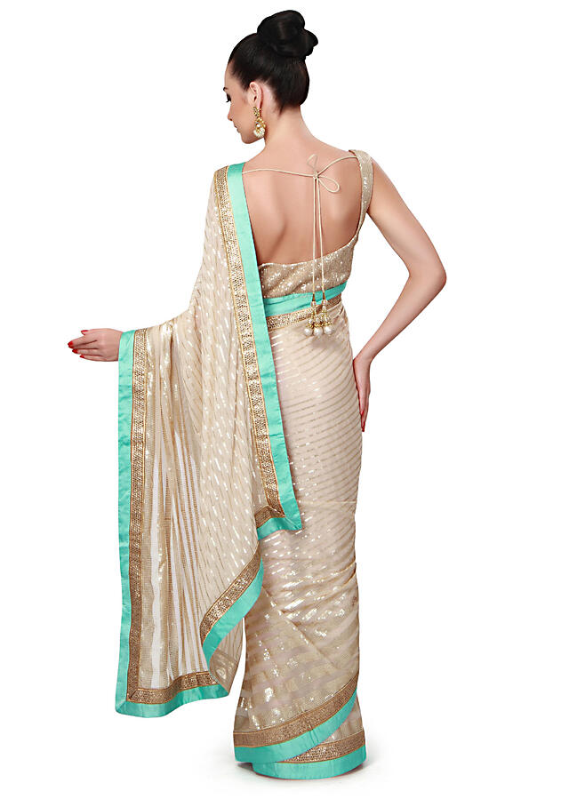 Beige saree adorn in sequin embroidery only on Kalki