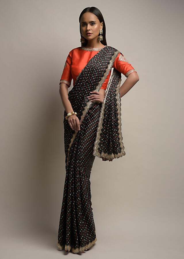 Black Saree In Satin Blend With Bandhani Print And Mirror Work Paired With Contrasting Coral Stitched Blouse Online - Kalki Fashion