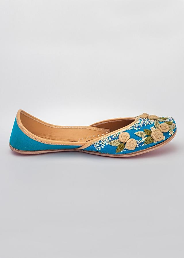 Blue Juttis In Raw Silk With Hand Embroidered Gold Fabric Flowers, Zardosi And Sequins Work By Vareli Bafna