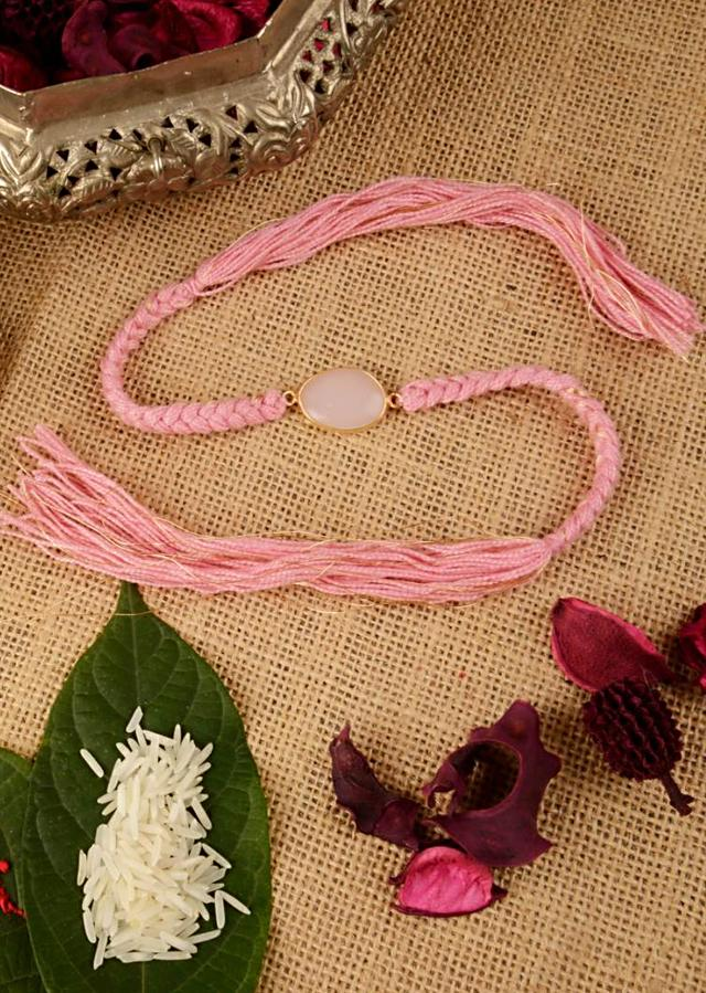 Blush Pink Rakhi Braided In Gold And Pink Thread And Further Enhanced In Semi-Precious Stone By Kohar
