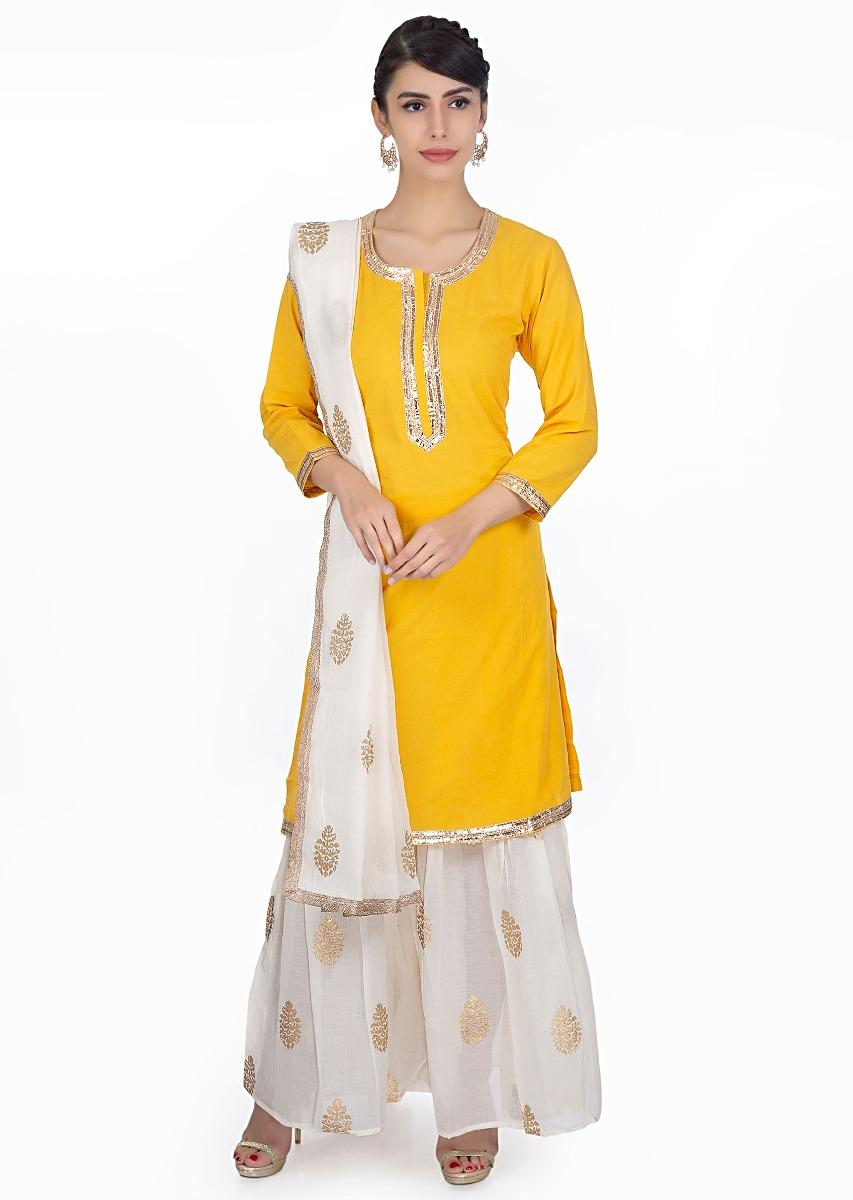 1c94e4c913 Chrome yellow cottons suit with a off white cotton sharara and dupatta in  foil printed butti ...