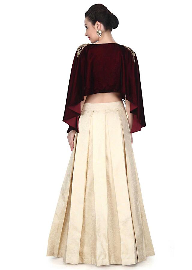 Cream lehenga matched with maroon cape only on Kalki