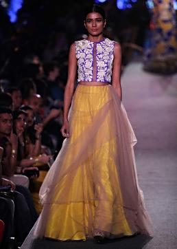 Model walks the ramp in beige lehenga with blue and yellow rose motif embroidery for Manish Malhotra Blue Runway collection at Lakme Fashion Week Summer Resort 2015