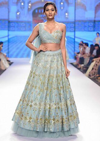 Aqua time blue raw silk lehenga teamed with one side strap bustier with georgette drape
