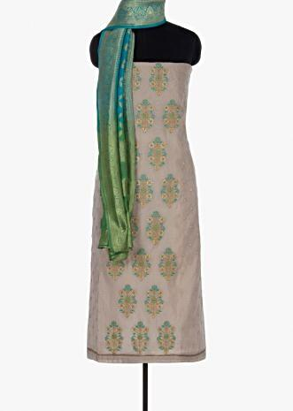 Beige unstitched suit paired with turq blue bottom and shaded brocade dupatta