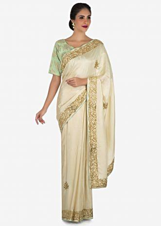 Cream saree in satin silk with a brocade blouse adorn in cut dana work only on Kalki