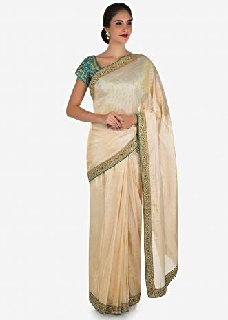 Cream saree with dark green blouse crafted in moti and cut dana embroidery work only on Kalki