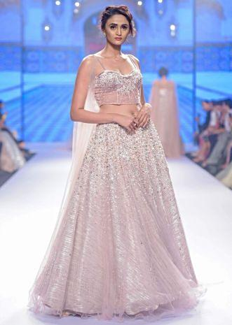 Dusty pink lehenga paired with multi paneled corset blouse  with attached net drape