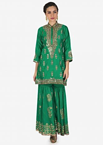 Featuring sharara suit in turq with kundan and zari embroidered placket and butti only on Kalki
