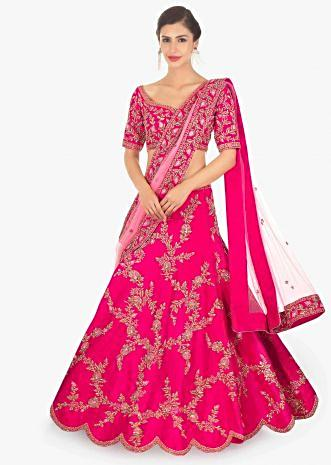 Fuschia pink raw silk lehenga and blouse paired with matching net dupatta