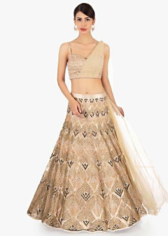 Gold net lehenga in geometric motif paired with a strap top with preattached net dupatta