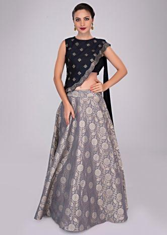 Grey brocade skirt paired with oxford blue crop top and embroidered asymmetric jacket