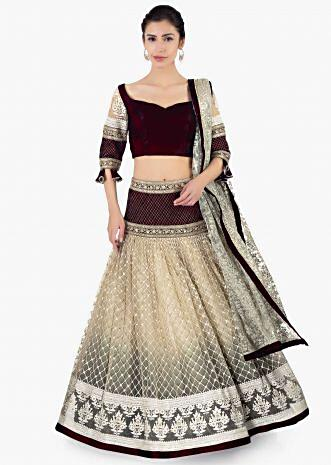 Maroon velvet blouse paired with lehenga in sequins and jaal work and a matching net dupatta