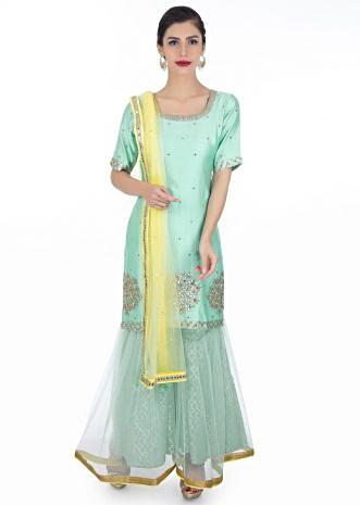 Mint blue embroidered silk suit paired with brocade lehenga in net lining and a contrasting yellow net dupatta