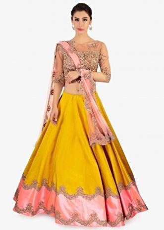 Mustard raw silk lehenga paired with a beige net blouse and pink net dupatta