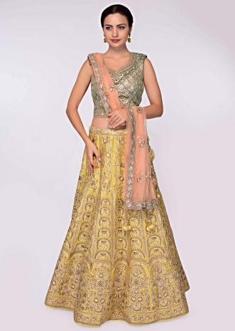 Olive green blouse paired with butter yellow heavy embroidered lehenga and coral peach net dupatta