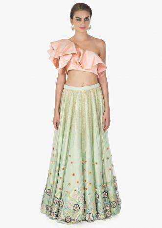 One shoulder ruffled peach crop top paired with Pista green net skirt in 3 D flowers