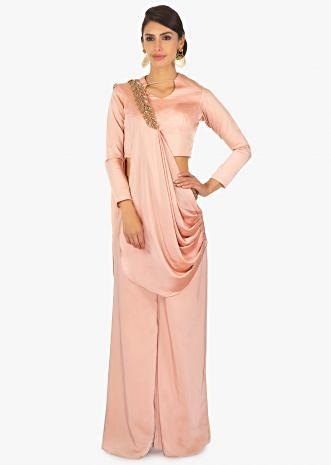 Peach milano satin pant with presttiched pleated applique dupatta paired with a matching peach blouse