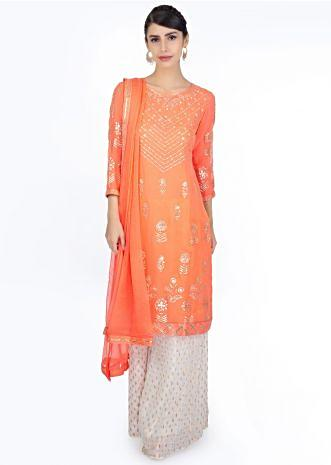 Peach zari embroidered suit paired with off white weaved palazzo and matching chiffon dupatta