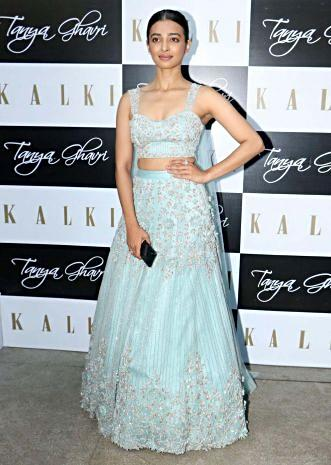 Mint green net lehenga set paired with a matching crop top with a pre attached fancy cape