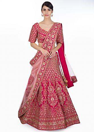 Rani pink raw silk heavily embellished lehenga paired with embroidered blouse and powder pink net dupatta