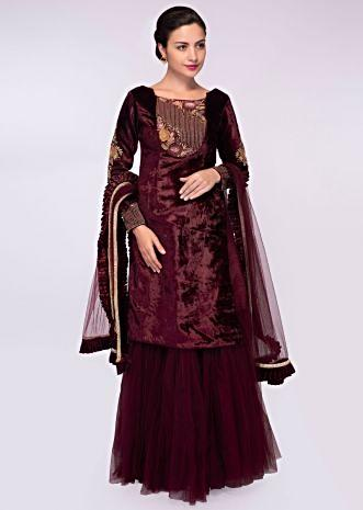 Raw silk lehenga with net gathers paired  with velvet long top and matching net dupatta