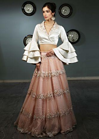 White satin blouse with layered frill sleeves paired with peach  net skirt in moti and sequins  embroidery