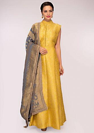 Yellow brocade anarkali dress matched with a grey georgette weaved dupatta