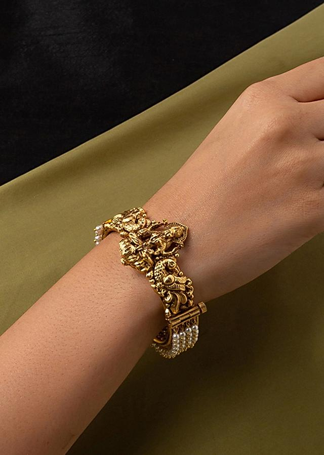 Gold Plated Bangle Designed With Carved Motifs And Studded With Shell Pearls Online - Joules By Radhika