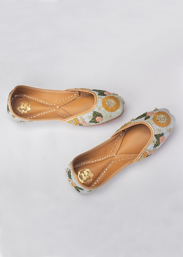 Powder Blue Juttis In Raw Silk With Bright Thread And Zari Embroidered Flowers By Vareli Bafna