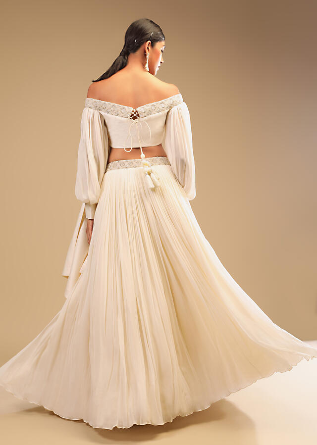 Powder White Lehenga And Off Shoulder Crop Top With Bishop Sleeves, Hand Embroidery And An Elaborate Bow Online - Kalki Fashion