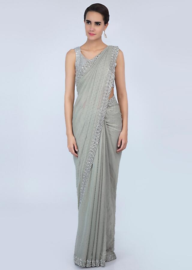 Sage green shimmer chiffon saree adorn with moti scattered and heavy stone embroidered border only on Kalki
