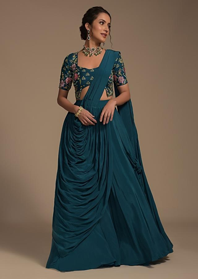 Teal Flared Lehenga Choli With Fancy Cut Out Hem And Attached Frill And Cowl Drape Online - Kalki Fashion