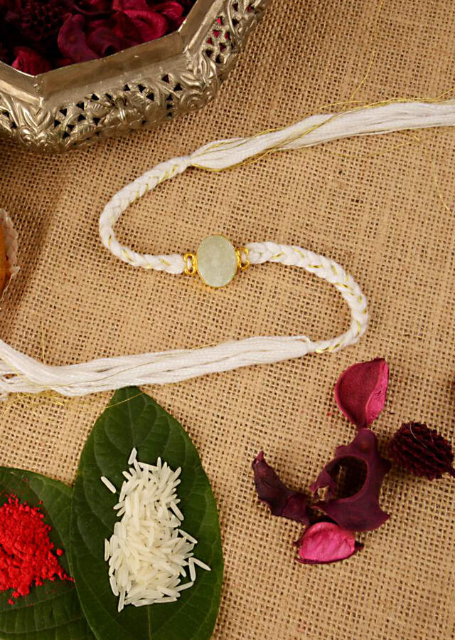 White Braided Rakhi In Gold And White Thread Work Is Further Enhanced In Semi-Precious Stone By Kohar