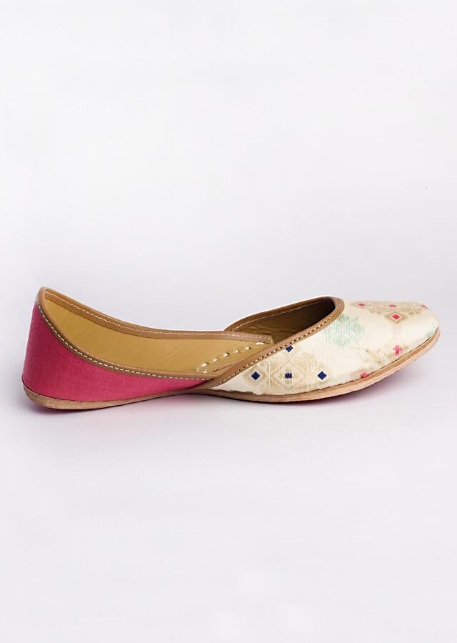 White Juttis In Patola Fabric With Hints Of Poppy Pink And Light Turquoise Blue By Vareli Bafna