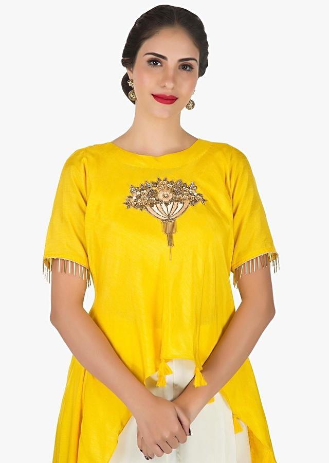 Yellow and white dhoti suit with a over layer embellished in resham and sequin butti work only on Kalki