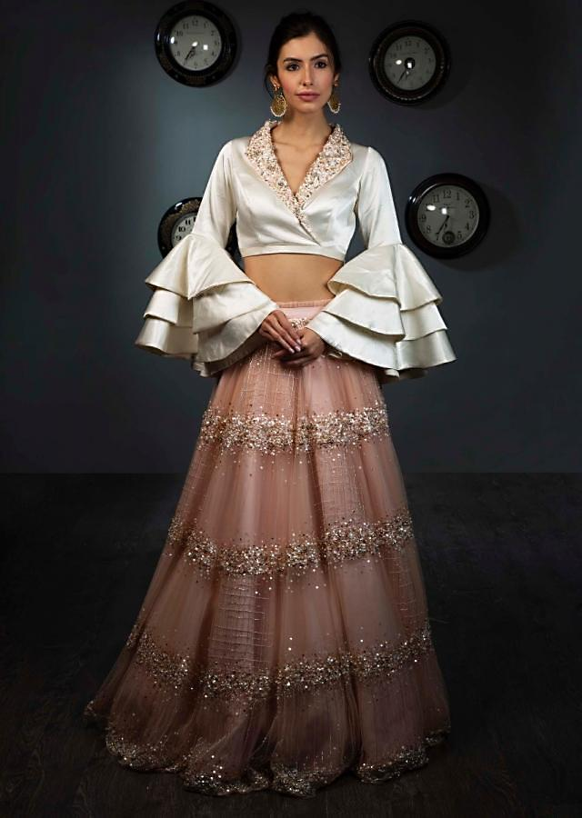 White satin blouse with layered frill sleeves paired with peach  net skirt in moti and sequins  embroidery only on Kalki