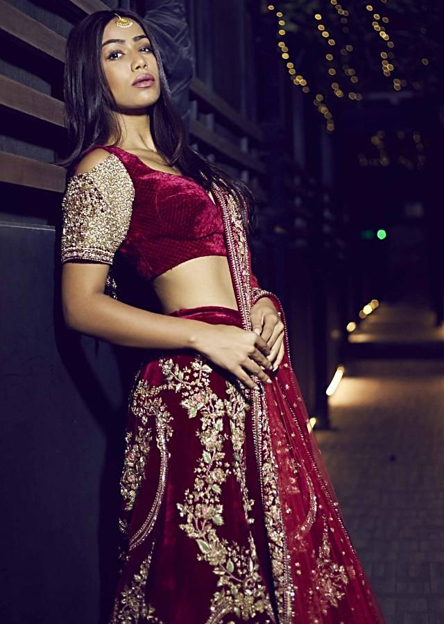 Featuring red velvet lehenga embellished in floral motif embroidery only on Kalki