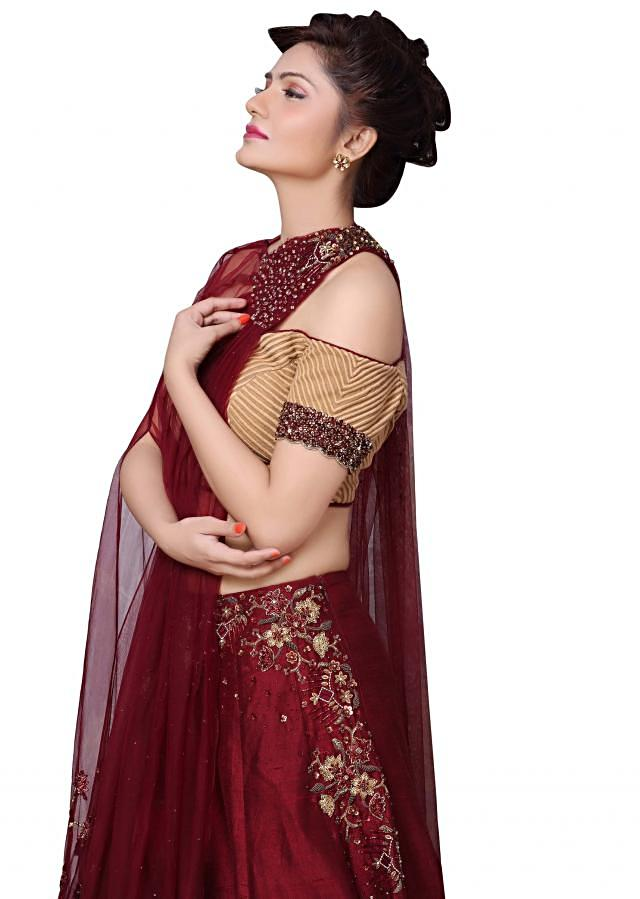 Maroon lehenga matched with one side fancy embroidered cape