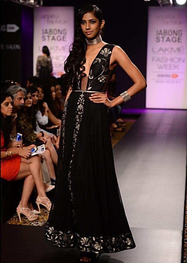Model walks the ramp in black embellished long jacket with beige and grey lehenga for Arpita Mehta