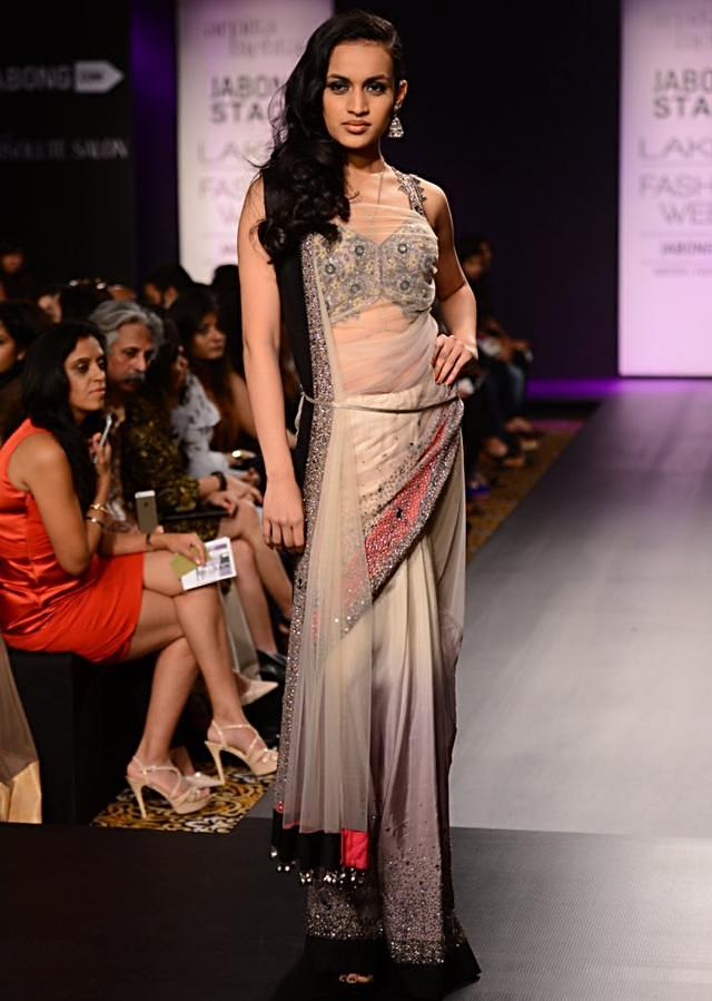 Model walks the ramp in beige and black floral embellished lehenga with contrast grey dupatta for Arpita Mehta