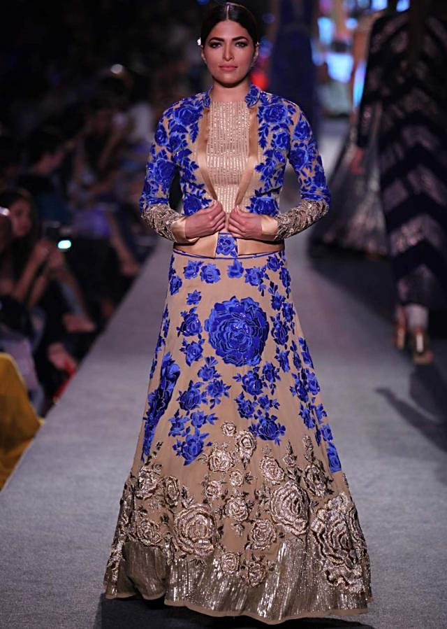 Model walks the ramp in beige lehenga adorn in blue and gold rose motif embroidery for Manish Malhotra Blue Runway collection at Lakme Fashion Week Summer Resort 2015