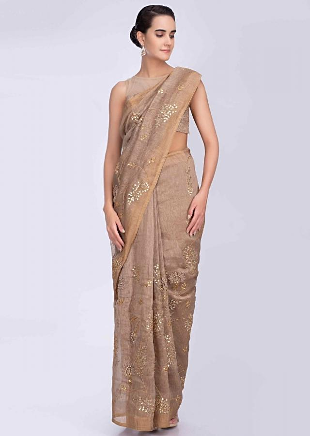 Beige linen saree with gotta jaal embroidery and floral applique work only on Kalki