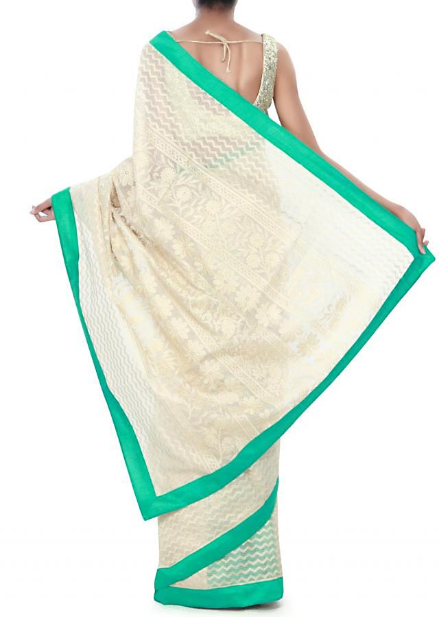 Beige saree adorn in thread embroidery only on Kalki