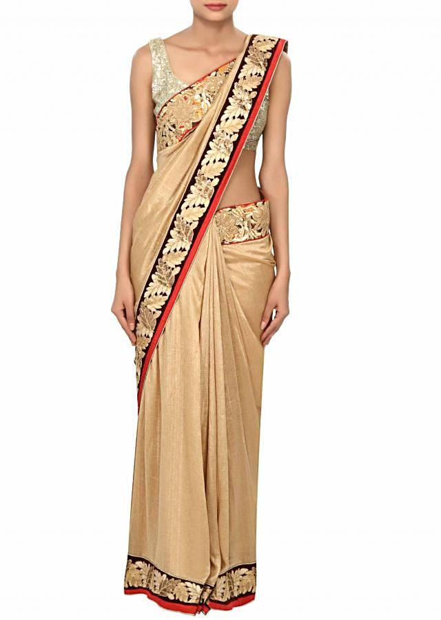 Beige saree enhanced in aari and sequin embroidery only on Kalki