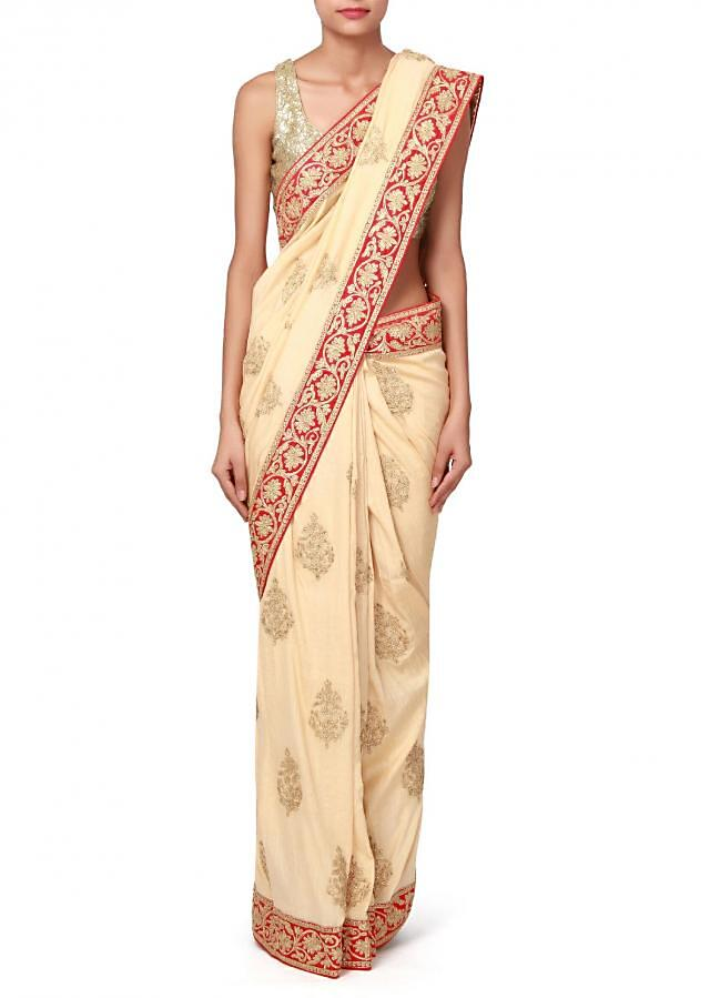 Beige saree enhanced in zari embroidered butti only on Kalki