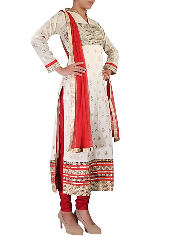 Beige straight fit suit adorn in zari embroidery.  only on Kalki