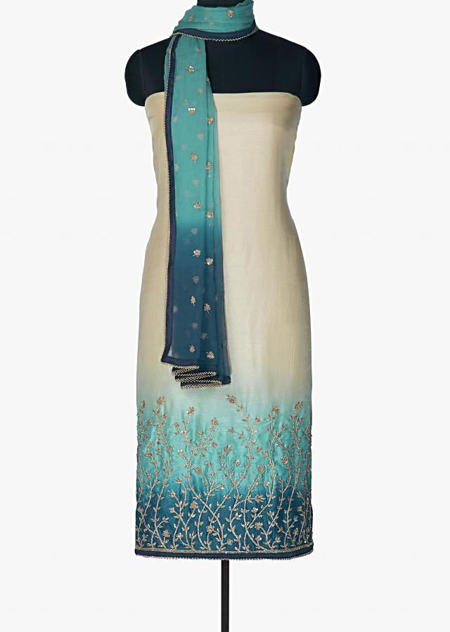 Beige and blue unstitched suit with hem line adorn in zari and sequin only on Kalki